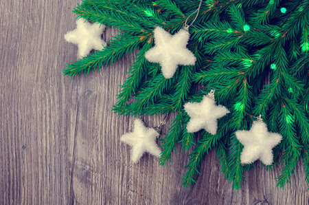 Christmas and new year composition. Green spruce branches with decoration on a dark wooden background. Design concept.
