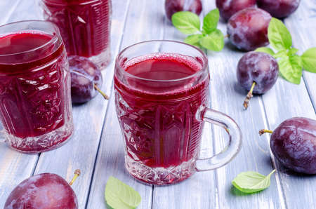 Red plum juice in glass on a blue wooden background with fresh fruit. Selective focus.