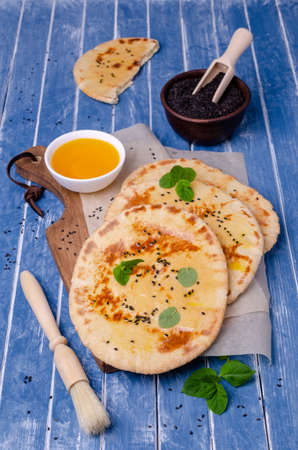 Traditional flatbread with oil, sesame and mint on a blue wooden background. Selective focus. Stock Photo