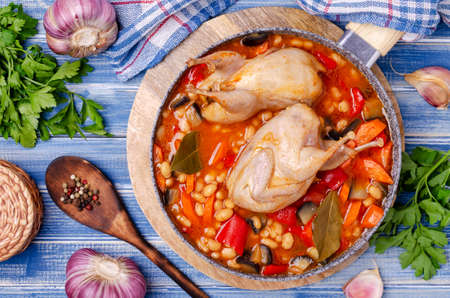 Stewed poultry with vegetables and beans in a dish on a blue wooden background. Selective focus.