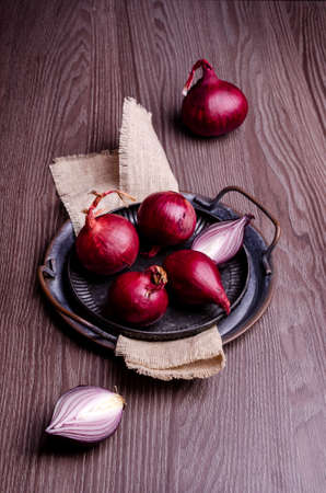 Raw red onion in a metal plate on a dark wooden background. Selective focus.