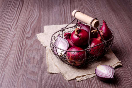 Raw red onions in a metal basket on a dark wooden background. Selective focus.