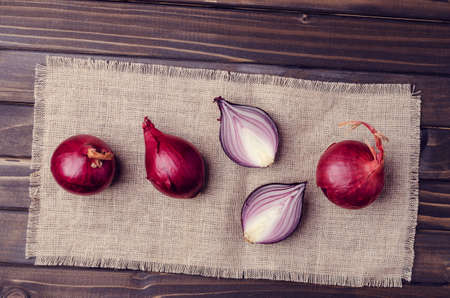 Raw red onion on textile burlap on a dark wooden background. Selective focus.