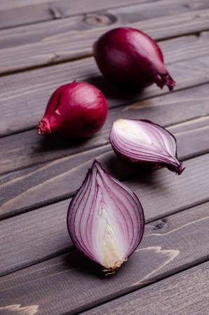 Raw red onion on a dark wooden background. Selective focus. 版權商用圖片