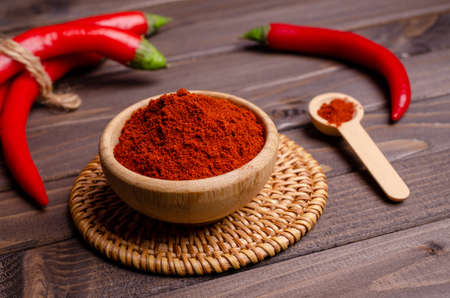 Red pepper powder in a bowl on a dark wooden background. Selective focus.