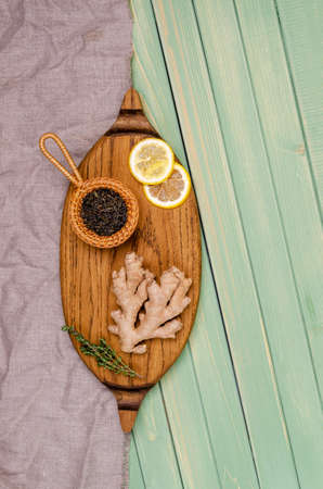 Dry tea with fresh spices on a green wooden background. Selective focus. Archivio Fotografico