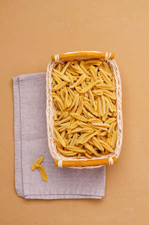 Yellow dry pasta in a wicker basket on a light stone background. Selective focus. Archivio Fotografico