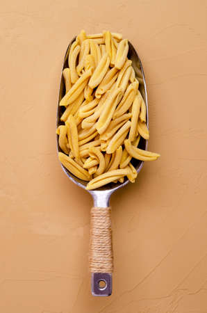 Yellow dry pasta in a metal scoop on a light stone background. Selective focus.