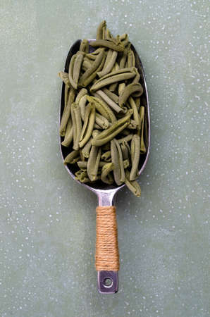 Green dry pasta in a metal scoop on a light stone background. Selective focus. Archivio Fotografico
