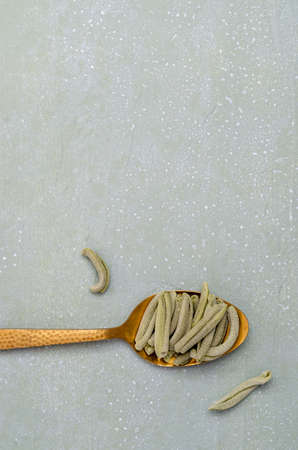 Green dry pasta in a metal spoon on a light stone background. Selective focus. Archivio Fotografico