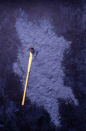 Traditional blue tea powder on a dark background. Selective focus.