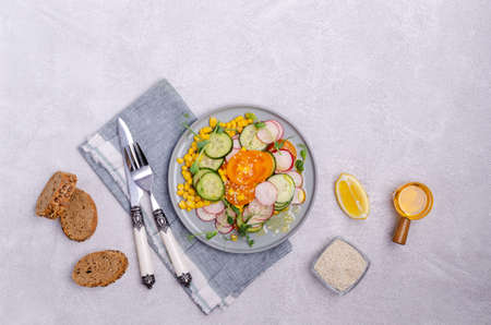 Vegetable salad with pea sprouts in a plate on a light stone background. Selective focus.