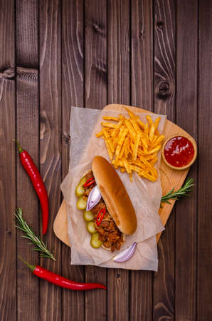 Sandwich with meat and vegetables and potato chips on a wooden background. Selective focus.