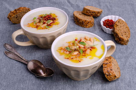 Vegetable cream soup with beans and spicy oil in a bowl on a textile background. Selective focus.