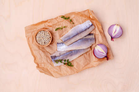 Fillet fermented herring with spices on paper. Top view. Selective focus. Stockfoto
