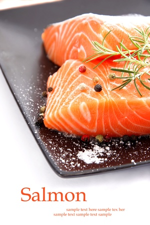 Nice pieces of raw salmon on white background photo