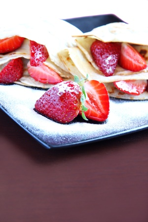Pancakes with strawberry and icing sugar photo