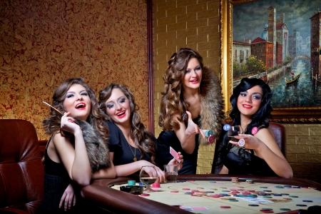 cartas de poker: Cuatro hermosas chicas juegan al póquer