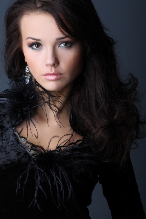 velvet dress: The beautiful girl with wavy hair in a black velvet dress with feathers