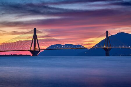 Sunset view on the bridge near Patras. Suspension bridge crossing Corinth Gulf strait, Greece, Europe. Second longest cable-stayed bridge in the world. Dramatic red sky under a Rion-Antirion Bridge. Imagens