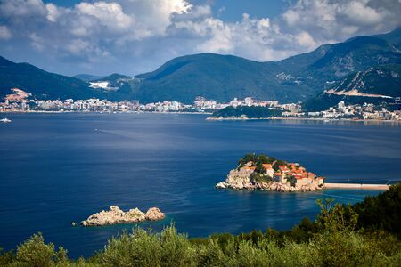 Amaizing sunset view on Sveti Stefan Island City. Small islet and resort in Montenegro. Balkans, Adriatic sea, Europe. Sunny day on the beach near the Saint Stefan island. Bridge on the old town on the island