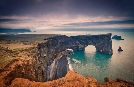 Famous tourist landscape with basalt rocky cape and ocean. Southern coast of Iceland. Black sand Beach View of peninsula Dyrholaey, Reynisdrangar, Vik, Iceland, Atlantic Ocean, Europe. Travel postcard