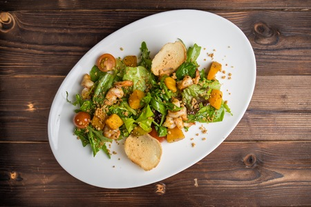 Salad with seafood and vegetable marrow decorated with croutons