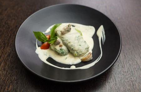 stuffed cabbage in a creamy sauce with basil and tomatoes