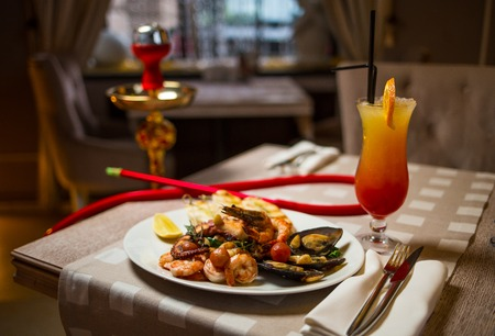 eastward: Relaxing table in a restaurant with seafood and hookah