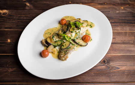 fish fillet with zucchini and tomatoes in a creamy sauce