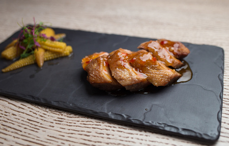 duck breast with sweet corn on a small board