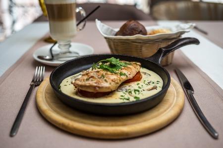 chicken fillet in a creamy mushroom sauce in a frying pan