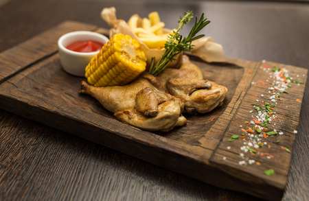 grilled chicken with fries and boiled corn Фото со стока