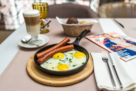 delicious breakfast of scrambled eggs with sausage in a restaurant