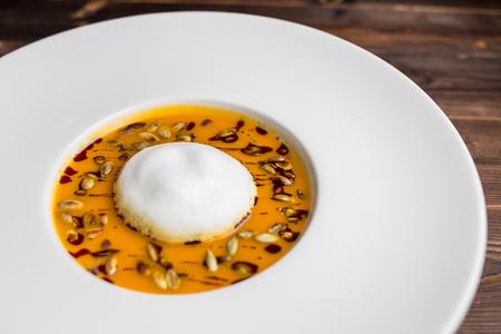 pumpkin soup with air foam and pumpkin seeds Фото со стока