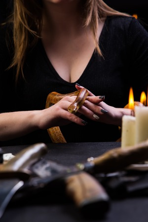 girl holds a snake in front of a table with knives
