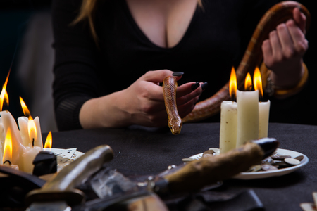 Magic ritual with a snake knives and coins Stock Photo