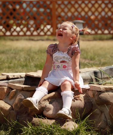 Image of a crying girl sitting on a rock Stock Photo - 5721626