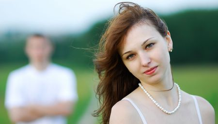 presentiment: The young beautiful woman and on a distant background the young man on a green field Stock Photo