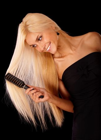 Nice young woman combs hair and smiles, it is isolated on black background. photo