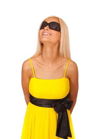 Young woman in yellow dress and sun glasses looks upwards and smiles, it is isolated on white background. Stock Photo - 6371986