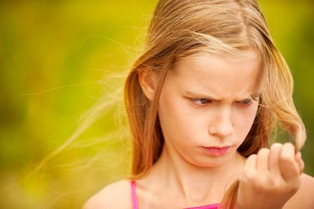 Little girl dissatisfied with brittle hair. photo