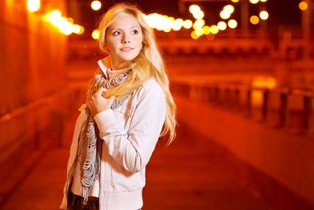 Beautiful fair-haired girl in evening in city which is shined by fires. photo