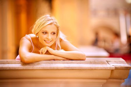 Young beautiful blonde on balcony leans elbows against handrail and smiles, it is isolated on white background. Stock Photo - 6457157