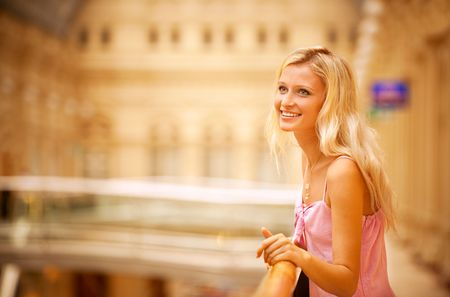 Beautiful girl leans against handrail in magnificent hall and laughs. Stock Photo - 6457192