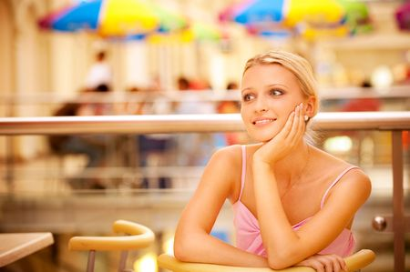 Charming girl sits at table in cosy cafe and smiles to thoughts. Stock Photo - 6457197