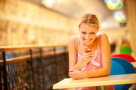 Beautiful young woman sits at little table, reads sms and smiles. photo