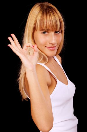 Casual woman smiling with her thumbs up, it is isolated on black background. photo