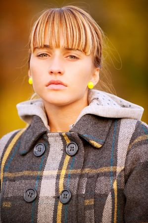 Beautiful young woman outdoors in autumn coat.  photo