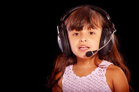 Young girl wearing phone headset, isolated on black background. photo